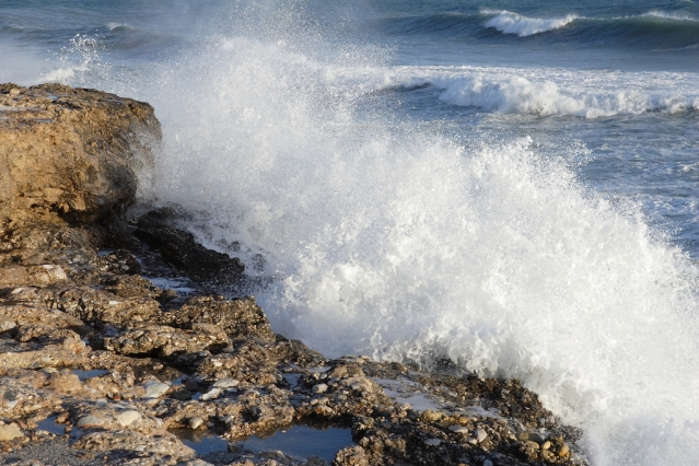 Mediterranean waves crashing over rocks in a storm