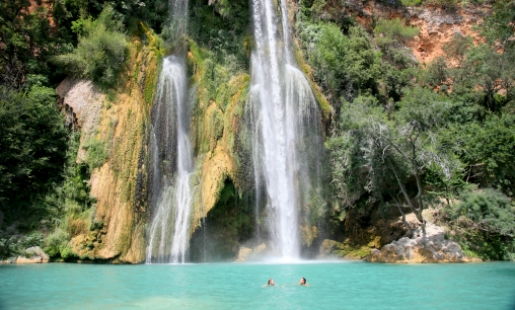 two people swimming in pool under waterfall