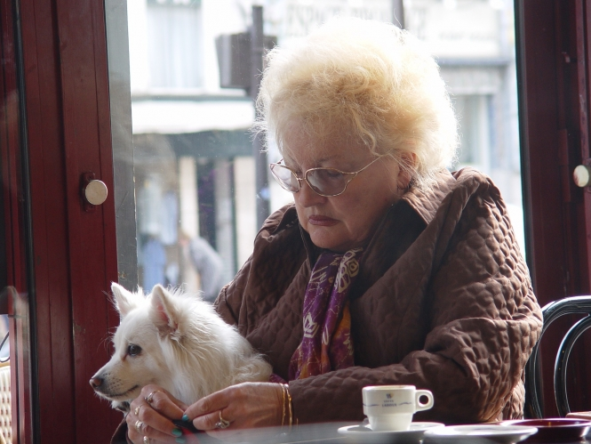 woman at restaurant table with coffee and dog