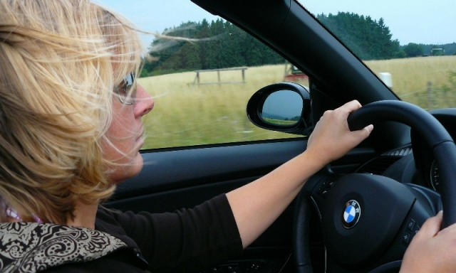 woman driving car blonde hands on wheel BMW looking left-right