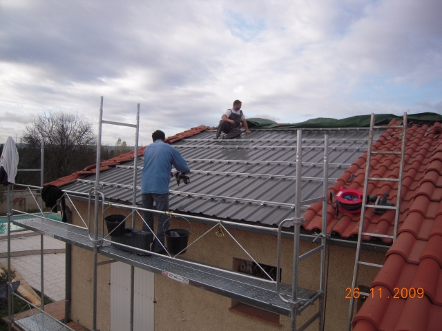 Two workers on a roof fitting red tiles from scaffolding